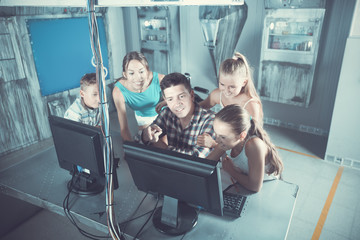 Family with kids using PC in  quest room under laboratory