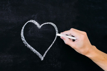 man's hand with white chalk drawing heart on blackboard as love symbol