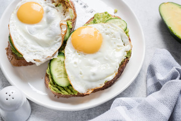 Egg and avocado breakfast toast on white plate. Closeup view. Healthy eating dieting concept