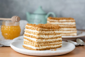 Honey layered cake or russian cake Medovik on white plate. Closeup view, selective focus