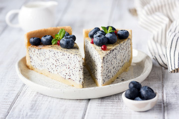 Cheesecake with poppy and blueberries. Homemade poppy pie on white plate decorated with blueberries and mint. Closeup view