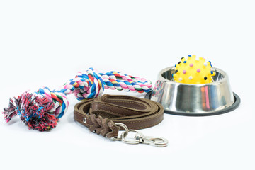 Pet supplies set about stainless bowl, rope, rubber toys and leather of leash for dog or cat on white background