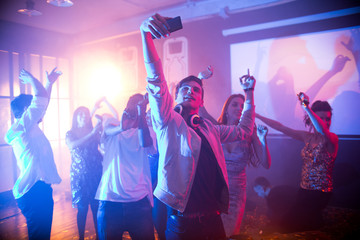 Crowd of trendy young people dancing in nightclub and enjoying party, focus on  handsome young man taking selfie on dance floor