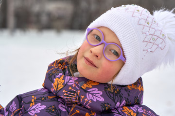 Portrait of a child girl in glasses on a winter walk.   The girl is dressed in a hat and jacket.   A cloudy winter day.  Close-up.