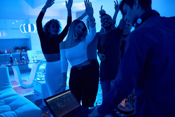 Group of modern young people dancing listening to DJ playing music at private house party, lit by blue light
