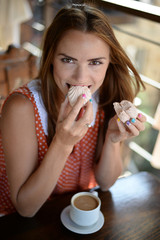 Beautiful young girl eating marshmallows in a cafe, portrait of a young woman in a candy closeup, girl having Breakfast in a cafe, emotional picture.