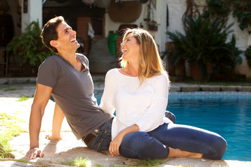 laughing couple sitting together outside by pool