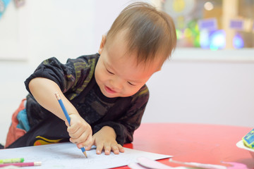 Cute little Asian 18 months / 1 year old toddler baby boy child drawing with pencil at art class, kid write with nursery teacher in a kindergarten,Creative play for toddlers concept - Selective focus