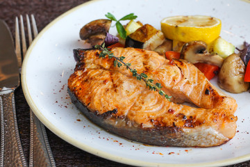 Grilled salmon steak served with vegetables - restaurant serve