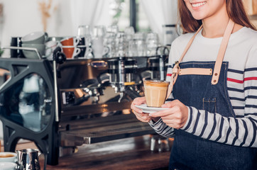 asia woman barista wear jean apron holding hot coffee cup served to customer with smiling face at bar counter,Cafe restaurant service concept.waitress working.