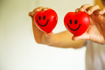 Two Red Smiling Hearts held by female nurse's hands, representing giving effort high quality service mind to patient. Professional, Specialist in white uniform concept