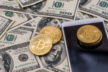 Bitcoin, smartphone on dollar bills
