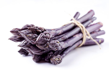 Row purple Asparagus as close-up with copy space – covered