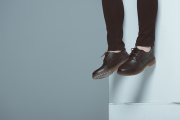 cropped view of man in trendy shoes on white cubes, isolated on grey Wall mural