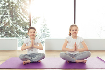 Group of children doing gymnastic yoga exercises at the winter resort with a beautiful view from the window. Two kids brother and sister doing lotus pose and smiling together