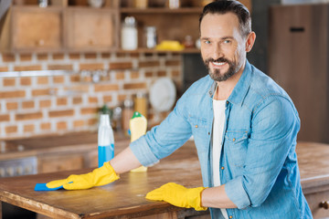 Cleaning in progress. Bearded attractive male cleaner using cleaning cloth while touching surface and gazing at the camera