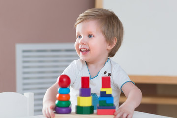 Two years old child boy playing with wooden colorful blocks and sorting shapes at home. educational toys concept. Development of kids fine motor skills, imagination and logical thinking