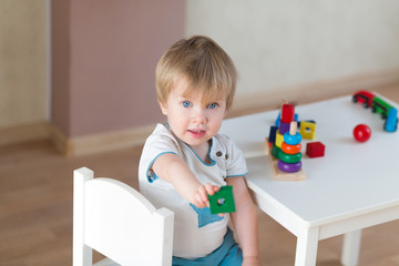 2 year-old child playing with educational cup toys at home. Little blond baby boy with blue eyes is playing with pyramid toy on the floor. Little kid have fun indoors