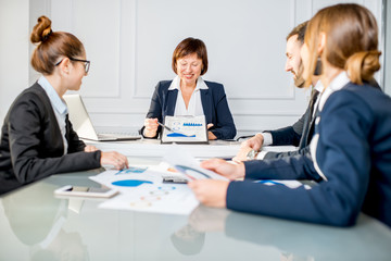 Senior businesswoman showing charts during the conference with young colleagues in the office