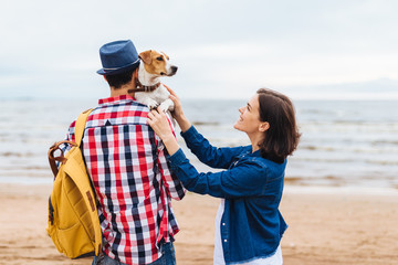 Outdoor shot of friendly family and their favourite dog come to sea to make photos and enjoy or breath fresh marine air, stand close to each other. People, holidays, recreation and leisure concept