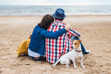 Lovely couple sit at beach near sea, embrace each other have pleasant conversation, being very romantic, admire beautiful nature and their little dog sits near its hosts. People, animals, love concept