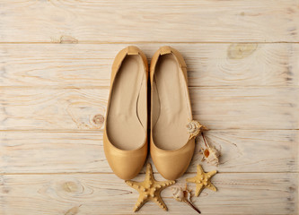 Fashion trend - women's shoes golden pearl color on a wooden background.