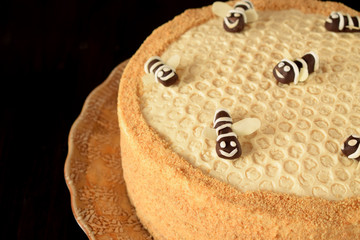 Honey cake Medovik decorated with bees made of chocolate on dark background