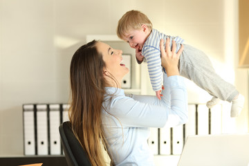 Working mother raising her baby son at office