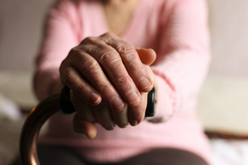 Close up of elderly woman holding a walking cane in nursing home.