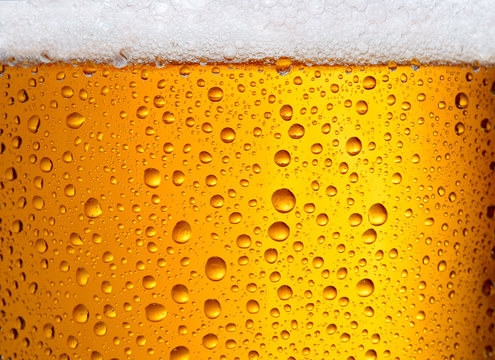 close-up view of glass of beer with big droplets and foam