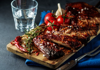 Delicious barbecued ribs seasoned with a spicy basting sauce and served with chopped fresh vegetables on an old rustic wooden chopping board in a country kitchen.