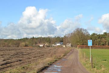 donkere wolken boven een boerderijtje aan een zandweg met verkeersbord in de Kruisbergse bossen