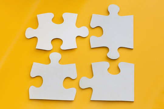 Four disconnected jigsaw puzzle pieces on yellow background. Concept of finding right solutions in teamwork.