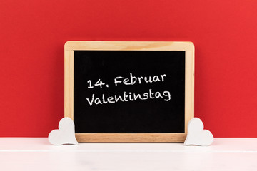 blackboard with hearts and red background with text 14. Februar Valentinstag (German for 14. february Valentine's Day)