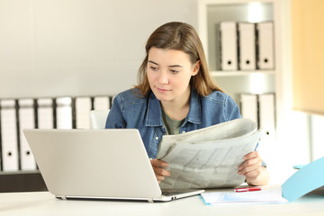 Intern comparing news in a laptop and newspaper