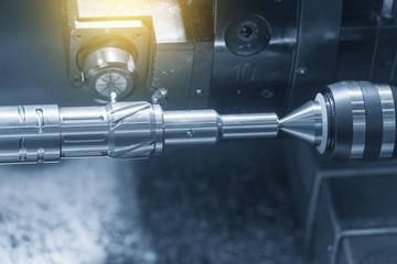 Close up of the CNC lathe (Turning machine)cutting brass shaft . Hi-precision CNC machining concept.