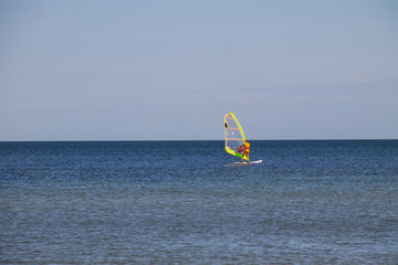 Windsurfing. Surfer exercising in calm sea or ocean.