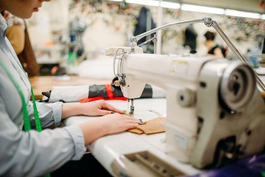 Tailor hands sews fabrics on a sewing machine