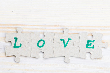 Word Love made of four pieces of jigsaw puzzle on light wooden table, close-up