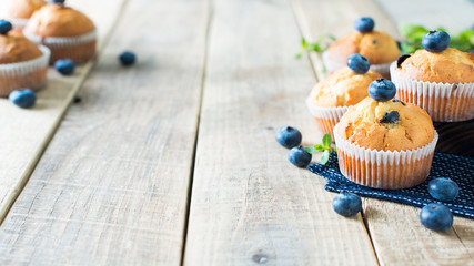 Blueberries muffins or cupcakes with mint leaves on wooden texture