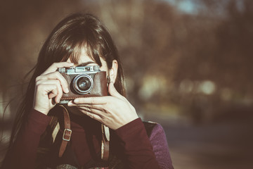Woman taking photo with old fashioned camera. Vintage photograpy