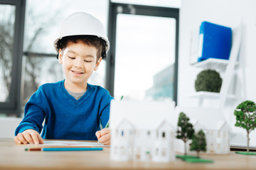Future engineer. Cute little boy in a white hard hat sitting at the table in the architects office and drawing a picture of a house