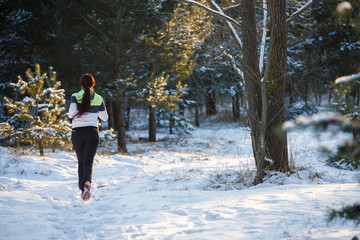 Image from back of young athlete walking through winter forest