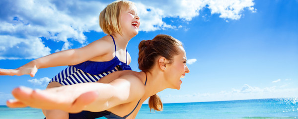 cheerful mother and daughter on seacoast having fun time
