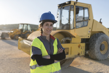 Worker woman posing near to construction vehicle