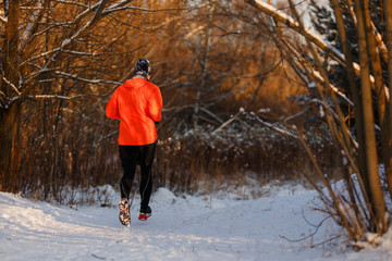 Photo from back of an athlete running through winter