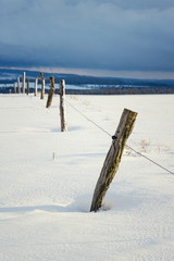 Vintage wooden fence poles in snowy winter country sunny day, weather forecast concept