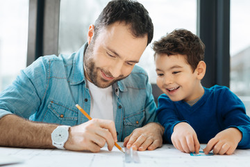 Under supervision. Upbeat little boy sitting at the table next to his father and watching him draw a blueprint with a pencil and a ruler