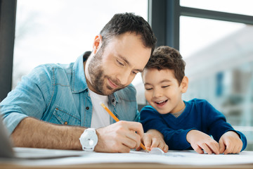 Interested glances. Cute chubby boy sitting at the desk next to his father and watching him draw a blueprint while smiling