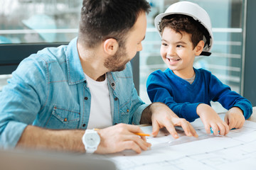 Best help. Adorable little boy sitting at the table next to his father and helping him to draw a blueprint while exchanging smiles with the man